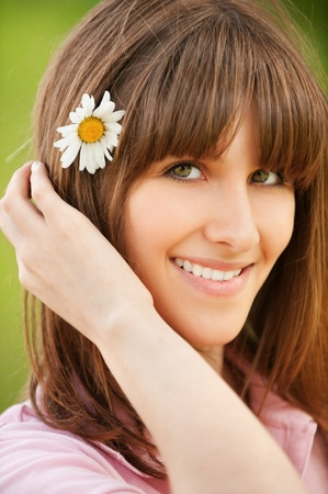 Closeup portrait of attractive young woman with flower in hair photo