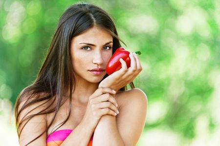 recreate: Portrait of young fair-haired woman holding Bulgarian pepper and looking somewhere at summer green park. Stock Photo