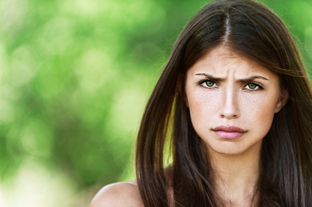 contracted: Beautiful young woman was offended, close-up on the green background of the summer. Stock Photo