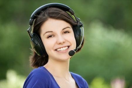Portrait of young smiling woman wearing headset standing at summer green park photo