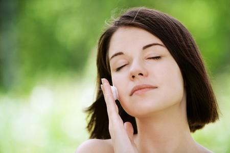 Close-up portret van jonge mooie brunette vrouw die witte crème op haar gezicht in de zomer groen park Stockfoto