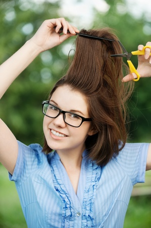 Portrait of young attractive brunette woman cutting her hair at summer green park photo