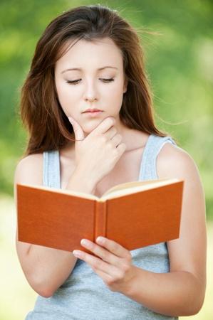 earnest: Retrato de atractiva libro de lectura seria ni�a, que llevaba camiseta gris en el verano de parque verde. Foto de archivo