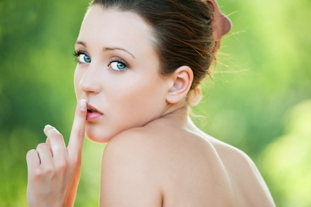 Portrait of a young beautiful, romantic, enigmatic woman holding finger near lips at summer green park photo