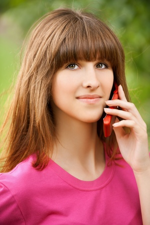 Portrait of beautiful young girl talking on the cell phone at summer green park photo