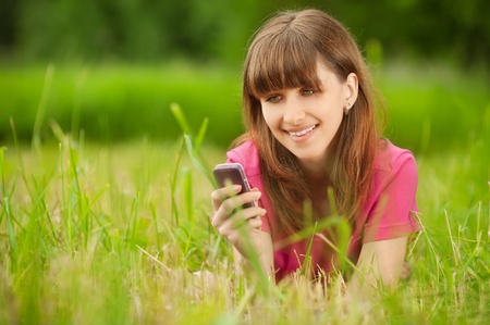 Beautiful young woman with mobile phone lies on green grass at summer green park photo