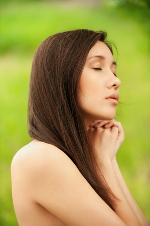ideal: Portrait of young asian woman with exposed shoulders in profile at summer green park Stock Photo