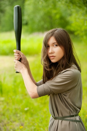 Portrait of young asian woman with bat standing at summer green park photo