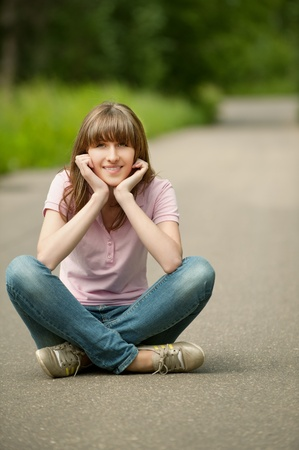 Young beautiful woman sits in lotus pose on road photo