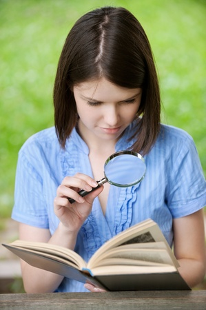 Portrait short haired young woman close-up reading book with a magnifier at summer green park photo