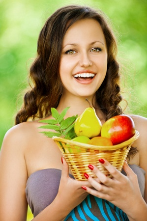 Portrait of beautifu young woman holding a basket of fruit at summer green park photo