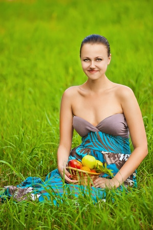 Portrait of a beautiful smiling young woman holding a basket of fruit sitting on grass at summer green park photo