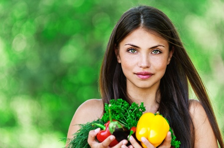 portrait of beautiful dark-haired smiling girl set with vegetables and herbs (eggplant, Bulgarian pepper red and yellow, dill and parsley) in hands on green background Stock Photo - 12473146