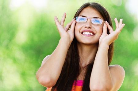 portret charmante jonge vrouw met een bril lachend. Achtergrond van de zomer de natuur Stockfoto