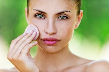 young woman closeup applying foundation photo