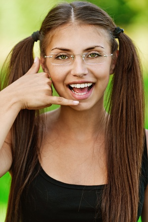 Portrait of young pretty fair-haired woman speaking on imaginary phone at summer green park. Stock Photo - 12473139