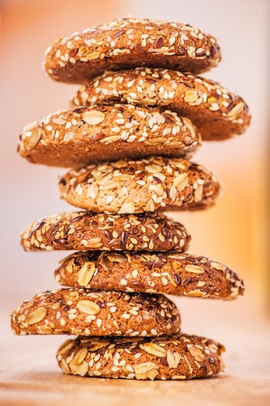 delicious oatmeal cookies with splash of sunflower seeds, sesame seeds on wooden table laid out in row photo