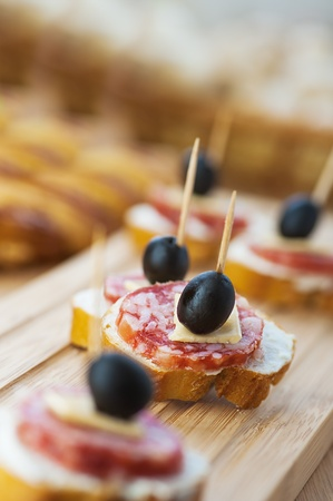 Sausage sandwiches, cheese and olives on toothpick, wooden table in background. photo