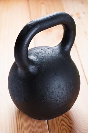 Large black cast iron weight on wooden floor in gym. photo