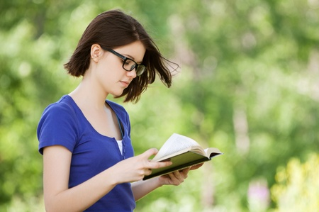 Portrait of beautiful young dark-haired pretty girl reading book at summer green park photo