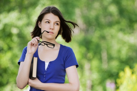 Portrait of young pretty woman wearing glasses holding book at summer green park photo
