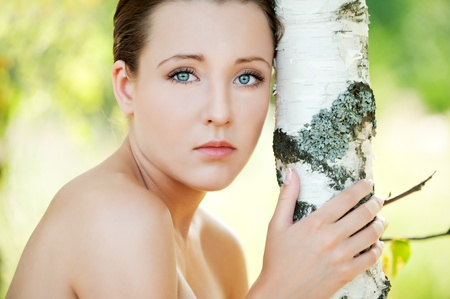 Portrait of pretty pensive young woman near birch tree at summer green park photo