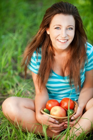 Portrait of pretty young woman sitting on green grass holding a basket with fruit and vegetables at summer green park Stock Photo - 12870659
