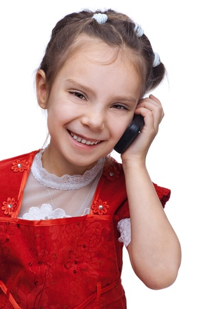Little smiling girl in red dress talking on cell phone, isolated on white background. photo