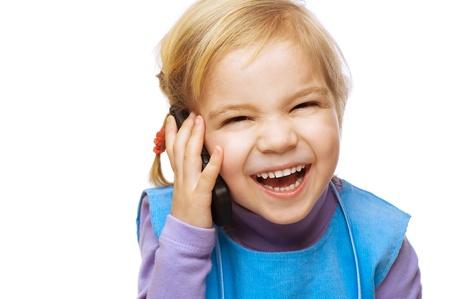 conversaciones: Niña riendo en el vestido azul hablando por teléfono celular, aislado en fondo blanco.