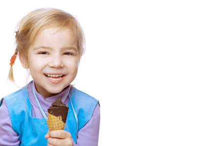 Little girl laughing in blue dress is eating ice cream, isolated on white background. photo