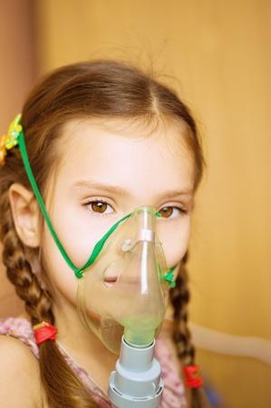 oxigeno: Pequeña niña con el inhalador en el hospital. Foto de archivo