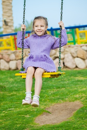 Little girl smiles and sits on swing in city park. photo