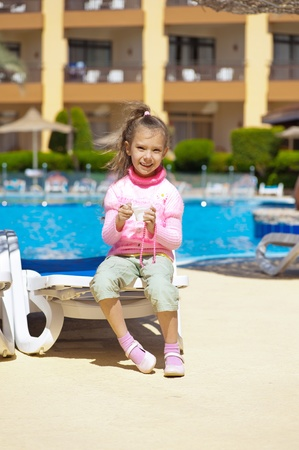 Small girl in pink sweater eating ice cream on background of pool at resort. photo