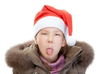 teases: Little girl in jacket and Christmas hat show tongue, isolated on white background. Stock Photo
