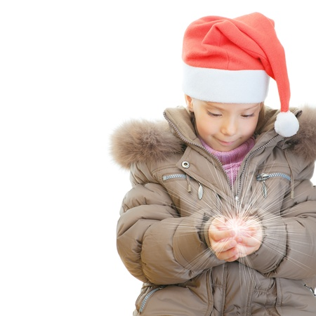 Little girl in jacket and Christmas hat keeps shining ball, isolated on white background. photo