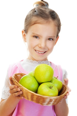 Little girl in pink dress holding basket of green apples, isolated on white background. Stock Photo - 12870600