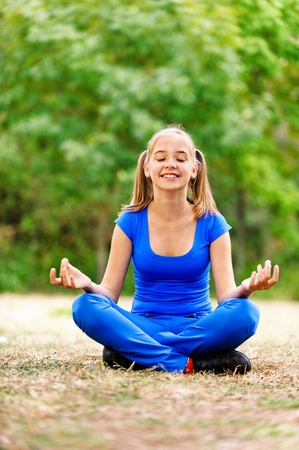 Smiling teenage girl in blue dress sitting in lotus position on green meadow in summer park.