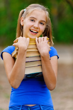 Teenager girl in blue dress holding stack of seven books and laughs in green summer park. Stock Photo - 13004126
