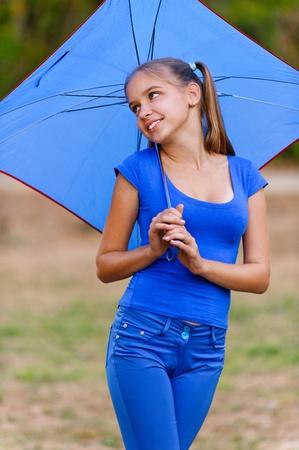 colegiala: Chica adolescente en el paraguas de vestir azul de la celebración, sonriente, verano en el parque verde. Foto de archivo