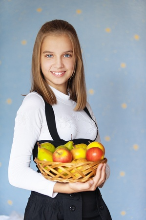 Beautiful blue-eyed smiling girl-teenager holding basket with apples, on blue background.