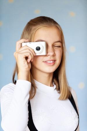 schoolgirl uniform: Beautiful girl-teenager photographed with camera, on blue background.