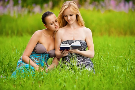 Two young beautiful girls reading book at summer green park photo