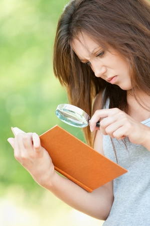 Portrait serious beautiful young woman magnifier regards book at summer green park photo