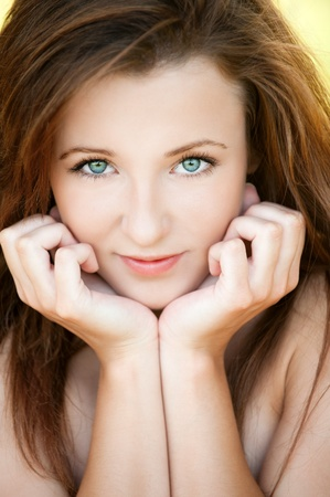 Portrait of beautiful attractive young woman propping up her face with hands at summer green park Stock Photo