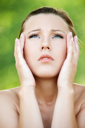 Young beautiful woman keeps hands for head and looks upwards at summer green park Stock Photo - 13002940