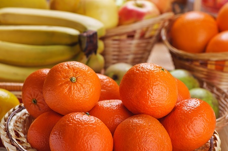Baskets of tangerines, bananas, apples and oranges on table. Stock Photo - 13004553