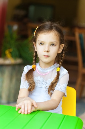 sits on a chair: Little girl sits at green childrens table and thinking.