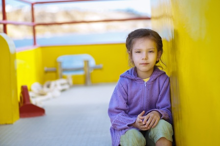 imperturbable: Little girl sitting on stern of ship step.