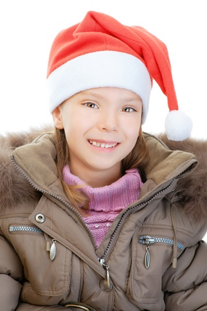 Little girl in jacket and Christmas hat smiling, isolated on white background. photo