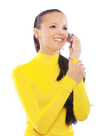 Portrait of smiling young beautiful woman in yellow turtleneck, who was talking on cell phone, isolated on white background. Stock Photo - 13052459